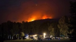 A wildfire burns on a mountain behind a home in Cache Creek, B.C., in the early morning hours of Saturday, July 8, 2017. (THE CANADIAN PRESS/Darryl Dyck)
