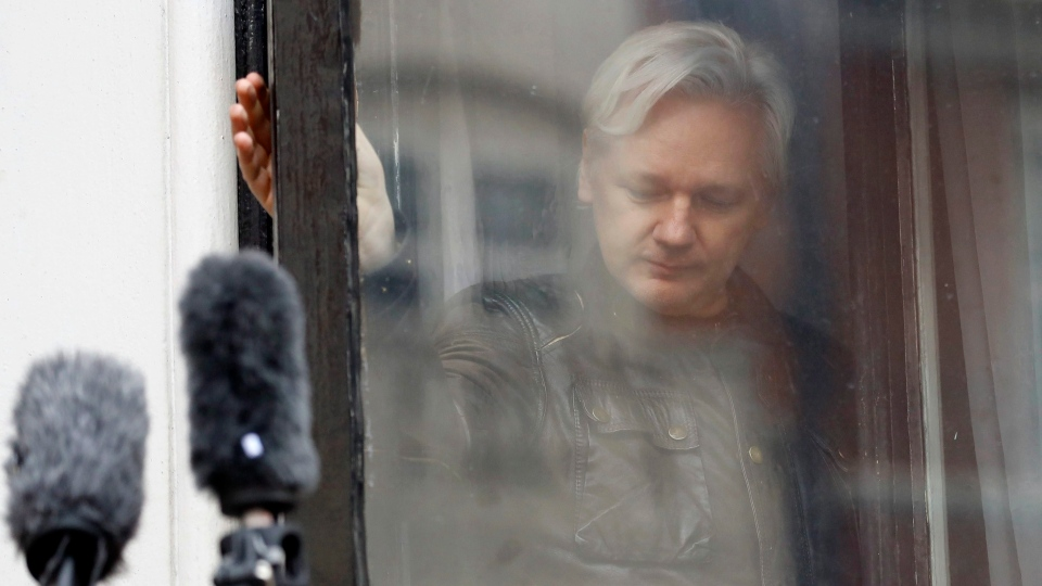 In this May 19, 2017 file photo, WikiLeaks founder Julian Assange closes a window after greeting supporters from the balcony of the London embassy in Ecuador. (AP Photo/Frank Augstein)