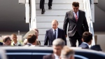 Russia's new ambassador to Finland Pavel Kuznetsov, background right escorts Russian President Vladimir Putin as he disembarks the plane at Helsinki airport in Vantaa, Finland, Monday, July 16, 2018. (Ronni Rekomaa/Lehtikuva via AP)