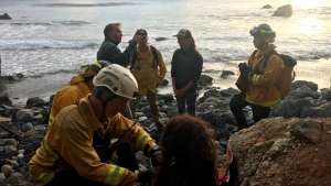 In this Friday, July 13, 2018, photo posted on the Monterey County, Calif., Sheriff's Office Twitter feed, authorities tend to Angela Hernandez, foreground centre, after she was rescued, in Morro Bay, Calif. Authorities say a couple on a camping trip came upon Hernandez, from Oregon, who had been missing since July 6, after her car went over a cliff in coastal California. (Monterey County Sheriff's Office via AP)