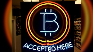 In this Feb. 7, 2018 file photo, a neon sign hanging in the window of Healthy Harvest Indoor Gardening in Hillsboro, Ore., shows that the business accepts bitcoin as payment. (AP Photo/Gillian Flaccus, File)