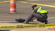 A member of the Calgary Police Service collects evidence at the intersection of Falconridge Boulevard and Falconridge Drive NE after a car struck two pedestrians