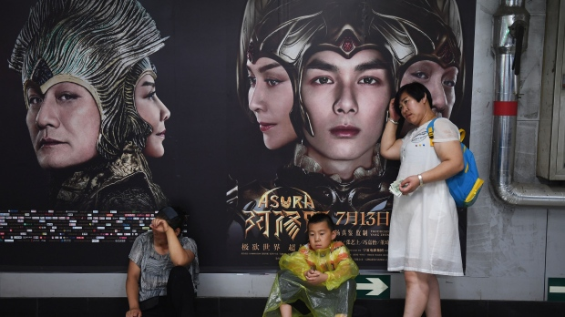 People rest in front of posters for the movie Asura at a subway station in Beijing. (GREG BAKER / AFP)