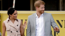 Prince Harry, right, and his wife Meghan the Duchess of Sussex wave at onlookers as they arrive for their visit to the launch of the Nelson Mandela Centenary Exhibition, marking the 100th anniversary of anti-apartheid leader's birth, at the Queen Elizabeth Hall in London, Tuesday, July 17, 2018. (AP Photo/Matt Dunham)