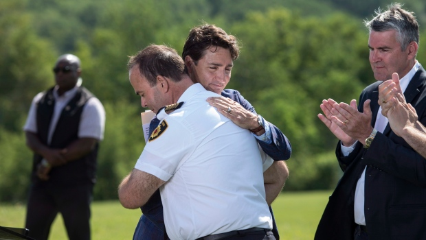 Prime Minister Justin Trudeau, centre embraces Joe MacDonald, Fire Chief for Barney's River, N.S., following an announcement with Nova Scotia Premier Stephen McNeil, right, of $90 million to improve the Trans-Canada Highway in the northeastern part of the province in Sutherlands River, N.S. on Tuesday, July 17, 2018. (THE CANADIAN PRESS/Darren Calabrese)