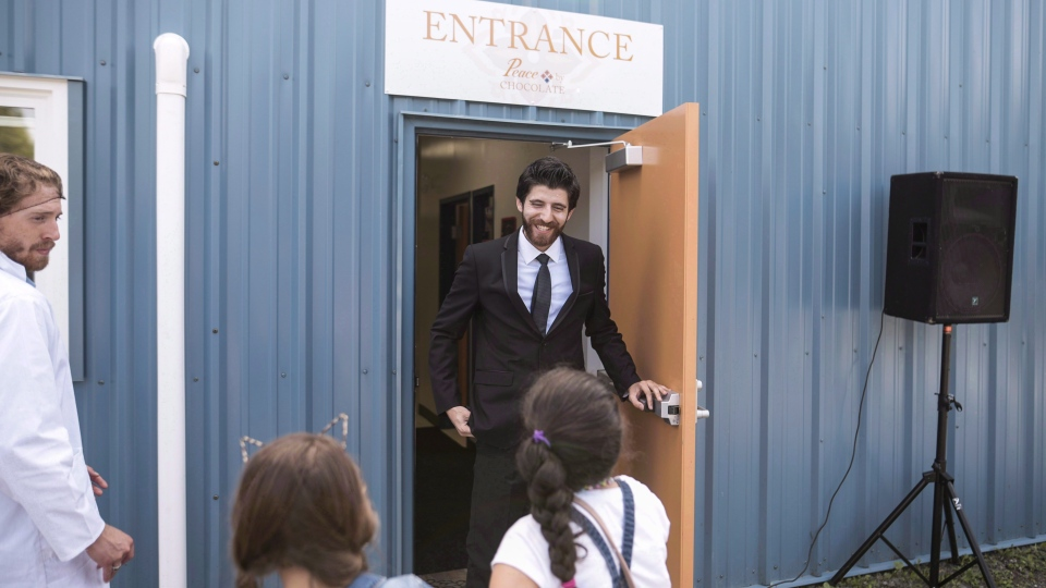 Syrian chocolatier Tareq Hadhad greets children at the door of Peace By Chocolate's factory in Antigonish, N.S. on September 9, 2017. (THE CANADIAN PRESS/Darren Calabrese)
