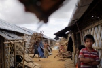In this June 28, 2018, photo, Rohingya refugees carry construction material through huts built in an extended area of Kutupalong refugee camp in Bangladesh. (AP Photo/Wong Maye-E)
