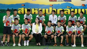 """Coach """"Ake"""" Ekkapol Janthawong, left, speaks on behalf of the 12 boys and himself and their cave rescue during a press conference discussing their ordeal in Chiang Rai, northern Thailand, Wednesday, July 18, 2018. (AP / Vincent Thian)"""