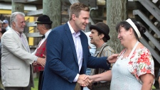 New Brunswick Premier Brian Gallant, followed by Quebec Premier Philippe Couillard, left, greets performers as they arrive for a meeting of Canadian premiers and Indigenous leaders at Le Pays de la Sagouine, a recreated historic Acadian village, in Bouctouche, N.B. on Wednesday, July 18, 2018. (THE CANADIAN PRESS/Andrew Vaughan)