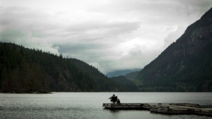 A man relaxes in a chair at the end of a dock over looking Buntzen Lake in Anmore, B.C. Tuesday, June 11, 2013. THE CANADIAN PRESS/Jonathan Hayward