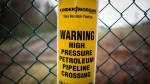 A sign warning of an underground petroleum pipeline is seen on a fence at Kinder Morgan's facility where work is being conducted in preparation for the expansion of the Trans Mountain Pipeline, in Burnaby, B.C., on April 9, 2018. THE CANADIAN PRESS/Darryl Dyck