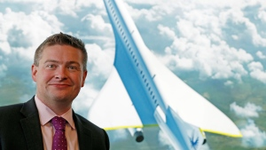 Boom Supersonic co-founder Blake Scholl poses for a photograph in front of an artist's impression of his company's proposed design for an supersonic aircraft, dubbed Baby Boom, at the Farnborough Airshow. (Adrian DENNIS / AFP)