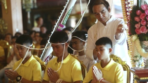 Coach Ekkapol Janthawong, centre, and members of the rescued soccer team attend a Buddhist ceremony that is believed to extend the lives of its attendees as well as ridding them of dangers and misfortunes in Mae Sai district, Chiang Rai province, northern Thailand, Thursday, July 19, 2018. (AP Photo/Sakchai Lalit)