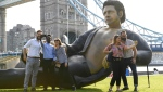 People take photos by a 25-foot statue of actor Jeff Goldblum in a pose from a scene in the first Jurassic Park movie, which has been created by a TV channel to celebrate the film's 25th birthday, at Potters Fields Park, London, U.K. (Doug Peters / THE ASSOCIATED PRESS)