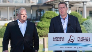 Ontario Premier Rob Ford, left, and Saskatchewan Premier Scott Moe talk with reporters as the Canadian premiers meet in St. Andrews, N.B. on Thursday, July 19, 2018.  (THE CANADIAN PRESS/Andrew Vaughan)
