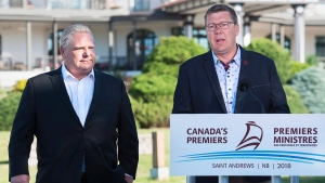 Ontario Premier Rob Ford, left, and Saskatchewan Premier Scott Moe talk with reporters as the Canadian premiers meet in St. Andrews, N.B. on Thursday, July 19, 2018. Ford and Moe have agreed to fight the federal government plan to impose a carbon tax. THE CANADIAN PRESS/Andrew Vaughan