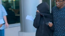 Leliqua Clarke covers her face while she leaves a Brampton courthouse on July 19, 2018 where she was granted $1,000 after being charged in connection with an assault at a Tim Hortons.