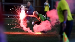 A security guard picks up a flare that was thrown onto the field during second half Canadian Championship soccer action between the Ottawa Fury FC and the Toronto FC, in Ottawa on Wednesday, July 18, 2018. THE CANADIAN PRESS/Justin Tang