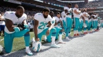 In this Sept. 11, 2017 file photo, from left, Miami Dolphins' Jelani Jenkins, Arian Foster, Michael Thomas, and Kenny Stills, kneel during the singing of the national anthem before an NFL football game against the Seattle Seahawks in Seattle. (AP Photo/Stephen Brashear, File)