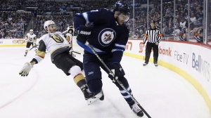 Vegas Golden Knights' Colin Miller (6) loses the fight for the puck against Winnipeg Jets' Adam Lowry (17) during second period NHL action in Winnipeg on February 1, 2018. (THE CANADIAN PRESS/John Woods)