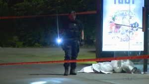 A Montreal police officer examines a street in Verdun where a man was shot