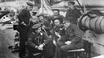 In this circa 1890 photo provided by the Naval History and Heritage Command, seven members of U.S. Navy sit together aboard the USS Enterprise in New York.  (Naval History and Heritage Command via AP)