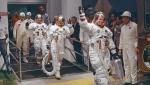 In this July 16, 1969, file photo, Neil Armstrong waving in front, heads for the van that will take the crew to the rocket for launch to the moon at Kennedy Space Center in Merritt Island, Fla.  (AP Photo/File)