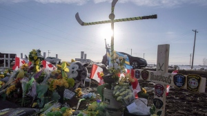 Hockey sticks, messages and other items continue to be added to a memorial at the intersection of a fatal bus crash that killed 16 members of the Humboldt Broncos hockey near Tisdale, Sask. on Saturday, April 14, 2018. THE CANADIAN PRESS/Liam Richards
