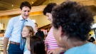 Prime Minister Justin Trudeau, left, hugs eight-year-old Carolina Portela, second right, as he meets with people at the Caldense Bakery in Bradford, Ont., on Friday, July 20, 2018. THE CANADIAN PRESS/Nathan Denette