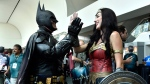 Armando Abarca, left, dressed as Batman, and Jessica Rose Davis, dressed as Wonder Woman, of Los Angeles, high five each other as they attend day one of Comic-Con International on Thursday, July 19, 2018, in San Diego. (Photo by Chris Pizzello/Invision/AP)