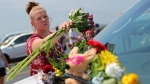 Jasmine Burkhardt leaves flowers on a car believed to belong to a victim of a last night's duck boat accident, Friday, July 20, 2018 in Branson, Mo. (AP Photo/Charlie Riedel)
