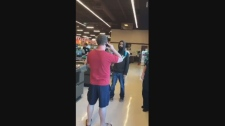 A man is seen in a Facebook video blocking the path of another man while at the checkout of a Sobeys in London, Ont. (Katie Pocasangre Montoya / Facebook)