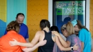 People pray outside Ride the Ducks, an amphibious tour operator involved in last night's duck boat accident on Table Rock Lake, Friday, July 20, 2018 in Branson, Mo. (AP / Charlie Riedel)