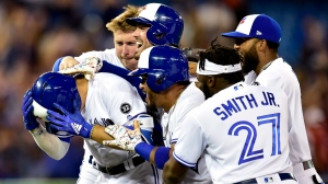 Toronto Blue Jays shortstop Aledmys Diaz (1) is mobbed by teammates after hitting the game-winning single scored by teammate Russell Martin, not shown, during tenth inning MLB baseball action against the Baltimore Orioles, in Toronto on Friday, July 20, 2018. (THE CANADIAN PRESS/Frank Gunn)