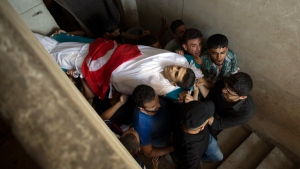 Palestinian mourners carry the body of Mohammed Badwan, 27, who was shot and killed by Israeli troops on Friday's ongoing protest at the Gaza Strip's border with Israel, into the family home during his funeral in Gaza City, Saturday, July 21, 2018. (AP Photo/Khalil Hamra)