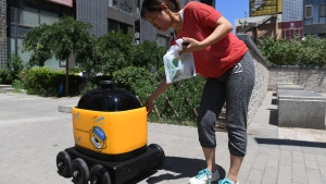 A woman picks up groceries delivered by a Zhen Robotics delivery robot at a residential compound during a demonstration of the robot in Beijing. (GREG BAKER / AFP)