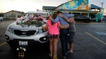 People pray by a car thought to belong to a victim of Thursday's boating accident before a candlelight vigil in the parking lot of Ride the Ducks Friday, July 20, 2018, in Branson, Mo.  (AP Photo/Charlie Riedel)