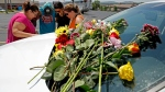 People pray next to a car believed to belong to a victim of a last night's duck boat accident, Friday, July 20, 2018 in Branson, Mo. The country-and-western tourist town of Branson, Missouri, mourned Friday for more than a dozen sightseers who were killed when a duck boat capsized and sank in stormy weather in the deadliest such accident in almost two decades. (AP Photo/Charlie Riedel)