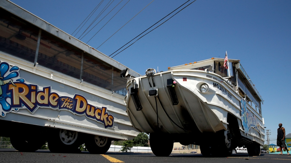 A man looks at an idled duck boat in the parking lot of Ride the Ducks Saturday, July 21, 2018 in Branson, Mo. (AP Photo/Charlie Riedel)