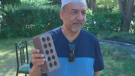 Abu Shiek holds up a brick that was allegedly thrown through his front window, after he was attacked leaving his mosque.