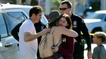 A Trader Joe's employee, right, hugs her loved ones after a gunman held dozens of people hostage inside a Trader Joe's supermarket before handcuffing himself and surrendering to police, Saturday, July 21, 2018, in Los Angeles. (Christian Monterrosa / THE ASSOCIATED PRESS)