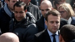 In this Wednesday April 26, 2017 file photo, Emmanuel Macron, right, is flanked by his bodyguard, Alexandre Benalla, left, outside the Whirlpool home appliance factory, in Amiens, northern France. (AP Photo/Thibault Camus)