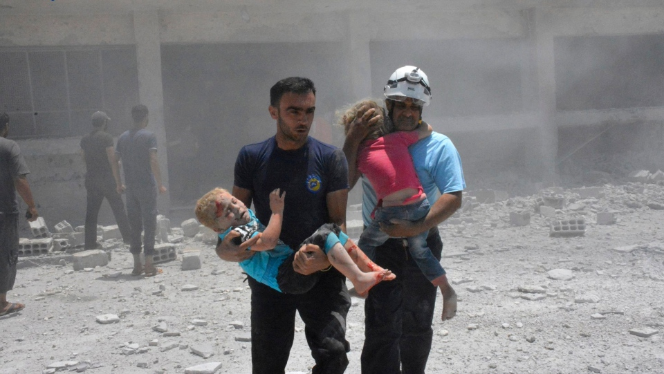 In this Wednesday, June 14, 2017, file photo, provided by the Syrian Civil Defense group known as the White Helmets, shows civil defense workers carrying children after airstrikes hit a school housing a number of displaced people, in the western part of the southern Daraa province of Syria. (Syrian Civil Defense White Helmets)