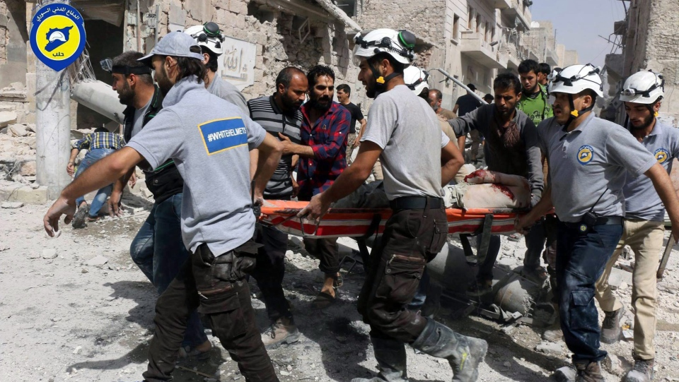 In this Wednesday, Sept. 21, 2016, file photo, provided by the Syrian Civil Defense White Helmets, rescue workers work the site of airstrikes in the al-Sakhour neighborhood of the rebel-held part of eastern Aleppo, Syria. (Syrian Civil Defense White Helmets via The Associated Press)