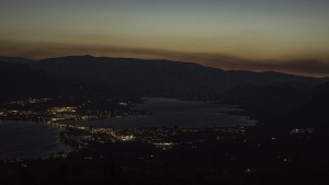 Looking high above the small town of Osoyoos B.C. in the southern Okanagan the glow of smoke and fire illuminates the night sky on Thursday July 19, 2018. THE CANADIAN PRESS/Jeff Bassett
