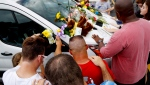 People pray around a van believed to belong to victims of a duck boat accident in the parking lot of the business running the boat tours Friday, July 20, 2018 in Branson, Mo. (AP Photo/Charlie Riedel)