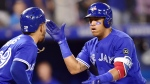Toronto Blue Jays third baseman Yangervis Solarte, right, celebrates his two-run home run against the Baltimore Orioles with teammate Devon Travis during eighth inning American League baseball action in Toronto on Sunday, July 22, 2018. THE CANADIAN PRESS/Frank Gunn