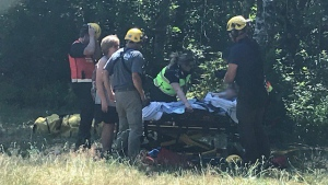 Members of Coquitlam Search and Rescue are seen with a subject near Buntzen Lake on July 22, 2018. (@CoquitlamSAR / Twitter)