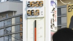 People watch the thermometer which reads 41.2 degree Celsius near Tajimi station, Gifu prefecture, central Japan on July 18, 2018. (Yoshiaki Sakamoto/Kyodo News via AP)