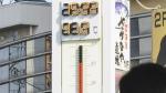 People watch the thermometer which reads 41.2 degree Celsius near Tajimi station, Gifu prefecture, central Japan on July 18, 2018. (Yoshiaki Sakamoto/Kyodo News via AP)
